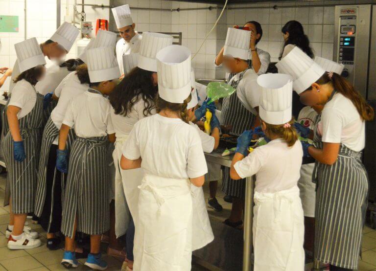 filoitoupediou.gr μικρά παιδιά σε κουζίνα  εστιατορίου κάνουνε μάθημα μαγειρικής με στολές και καπέλα σεφ  | YouBeHero