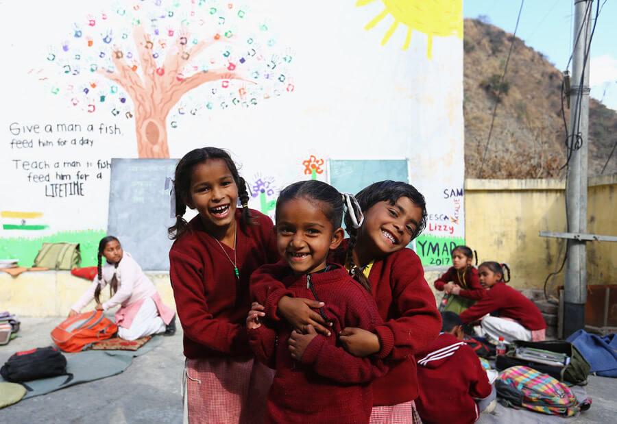 actionaid.gr παιδιά στην Αφρική χαμογελάνε παίζουνε στο διάλειμμα με ζωγραφισμένο τον τοίχο πίσω τους  | YouBeHero