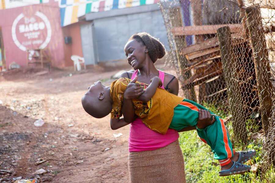 actionaid.gr μητέρα στην Αφρική κρατάει το παιδί της αγκαλιά χαρούμενη | YouBeHero