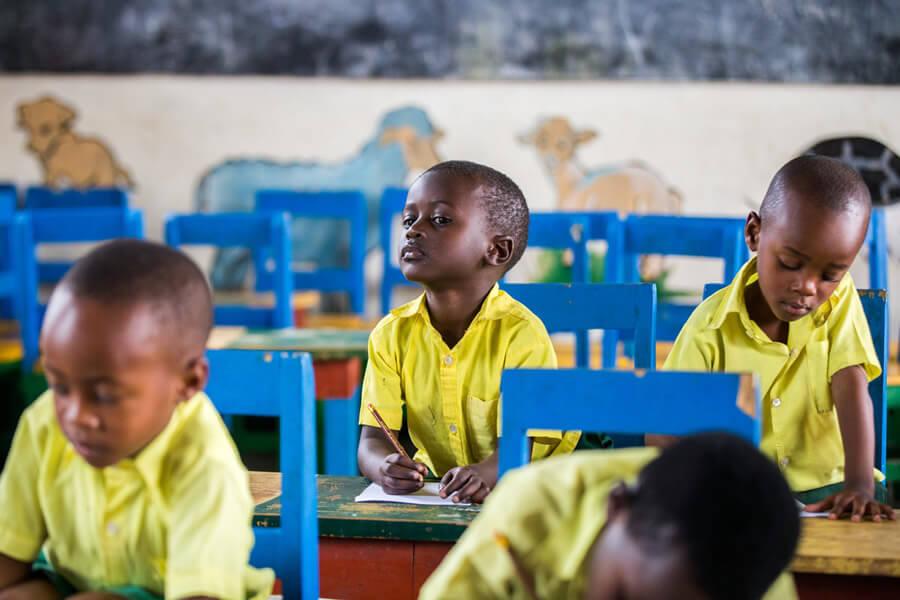 actionaid.gr παιδιά στην στην τάξη με κίτρινα πουκάμισα και μπλε καρέκλες | YouBeHero