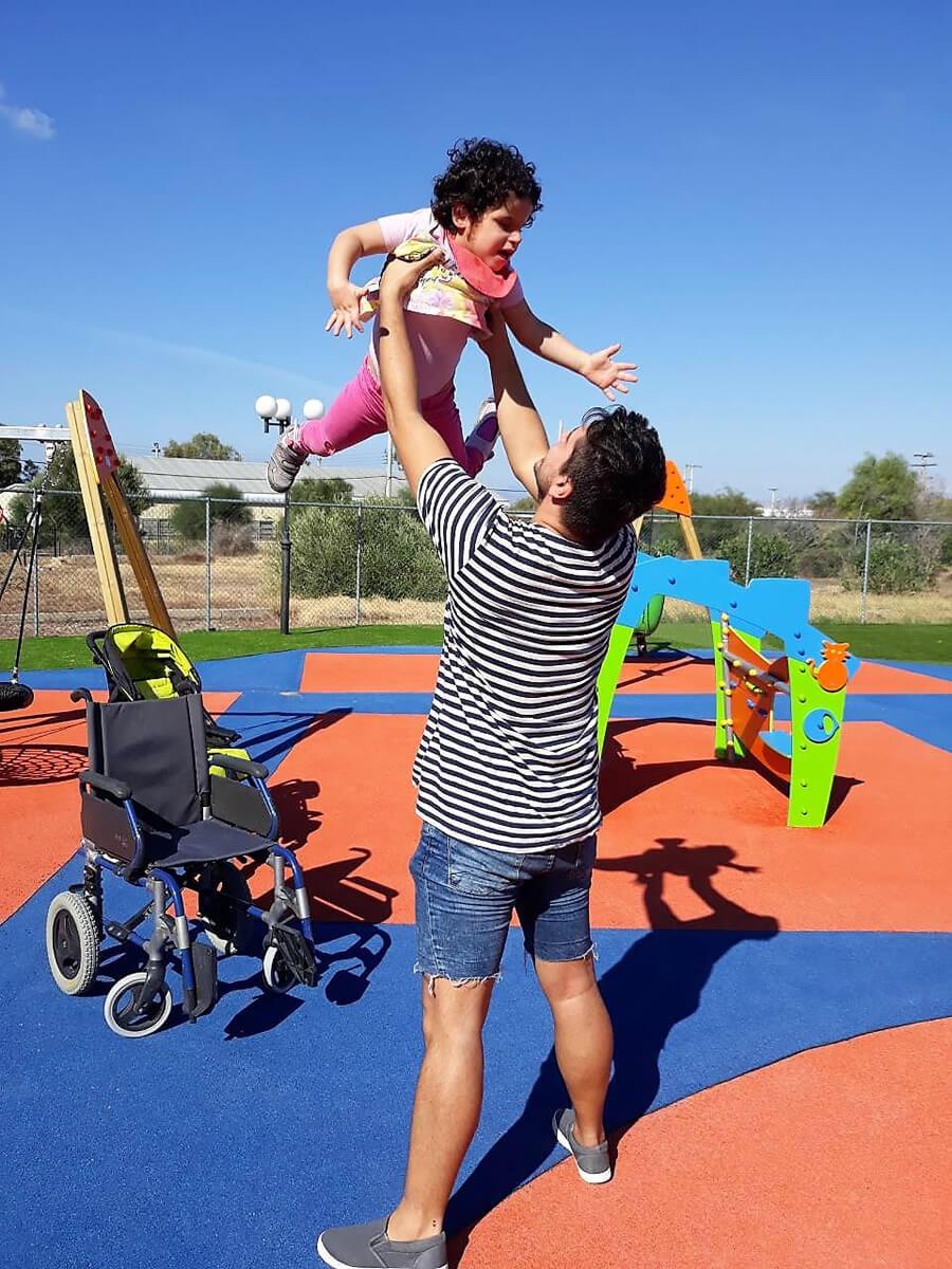 amimoni.gr άνδρας κρατάει ψηλά ένα παιδάκι στην παιδική χαρά, αναπηρικό αμαξίδιο  | YouBeHero