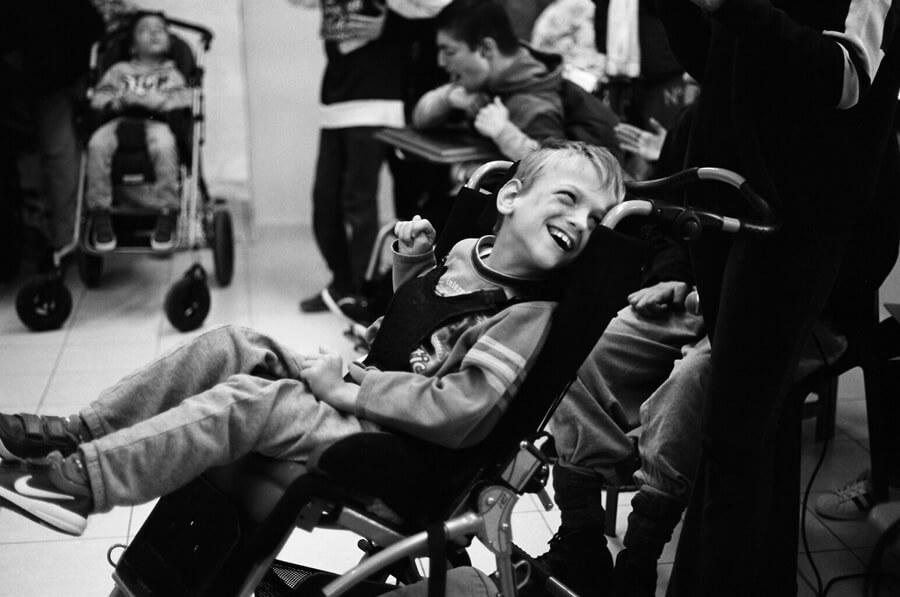 amimoni.gr παιδάκι σε ειδικό αναπηρικό αμαξίδιο χαμογελάει   | YouBeHero