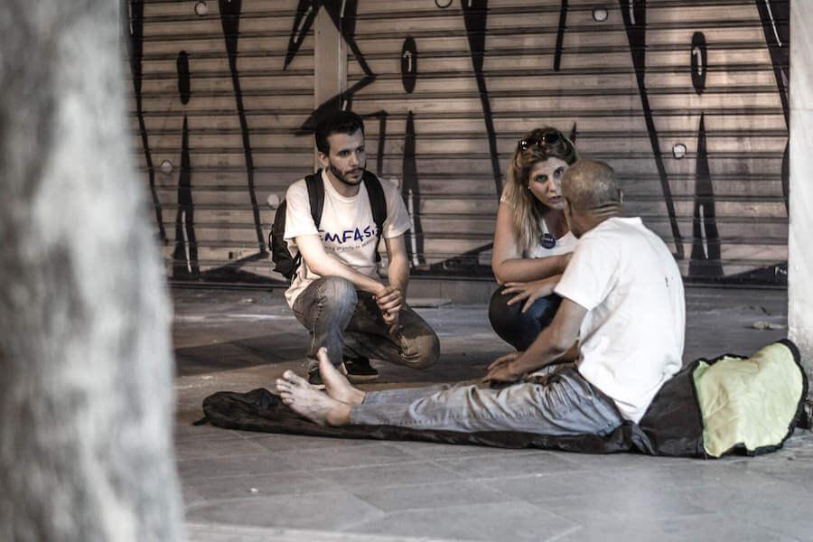 Εθελοντές του emfasisfoundation.org φροντίζουν άστεγο που κοιμάται στον δρόμο πάνω σε χαρτόνια  | YouBeHero