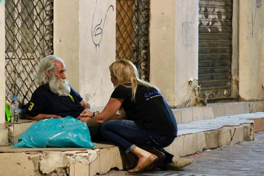 Εθελόντρια του emfasisfoundation.org προσεγγίζει άστεγο ξαπλωμένο στο πεζοδρόμιο με μία σακούλα γεμάτη ρούχα και είδη πρώτης ανάγκης | YouBeHero