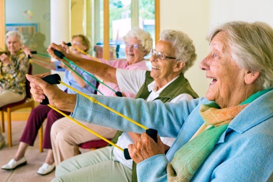 frodizo.gr  ηλικιωμένες γυναίκες κάνουνε ασκήσεις με λάστιχα  σε κατ'οίκον παρέμβαση για την άνοια   | YouBeHero
